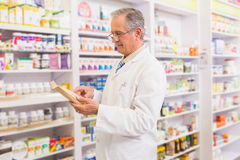 Prescrizione senior sorridente della lettura del farmacista Immagini Stock Libere da Diritti