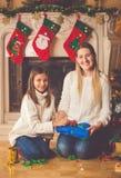 prese愉快的母亲和女儿包装的圣诞节的被定调子的图象 免版税图库摄影
