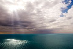 Presence of god. Light push through the clouds to the sea Stock Photography