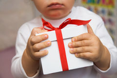 Present. The small child presses to itself a beautiful gift Royalty Free Stock Image