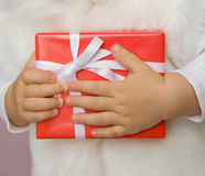 Present. The small child presses to itself a beautiful red gift Stock Photo