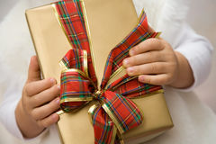 Present. The small child holds a beautiful present in the hands Royalty Free Stock Photo
