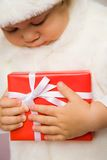 Present. The small child presses to itself a beautiful red gift Stock Image