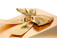 Present. A gift of attention in gold color with a decorative ribbon Stock Photo