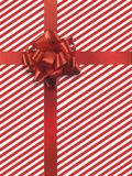 Present 3. Red ribbon over red and white striped paper Royalty Free Stock Photography
