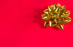 Present. Shiny golden bow on a bright red surface Royalty Free Stock Photography
