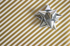 Present. Golden striped wrapping  paper with a silver bow Stock Photography