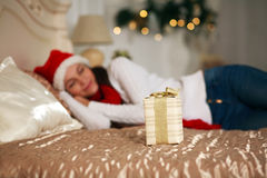 Present on the background of a sleeping girl on bed Royalty Free Stock Image