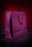 Present bag. Papper present bag on wooden table top and dark background royalty free stock photography