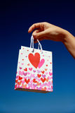 Present bag with heart in hand on blue sky Royalty Free Stock Images