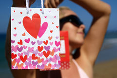 Present bags with hearts in hands of sexy woman Stock Images
