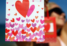 Present bags with hearts in hands of sexy woman Stock Image