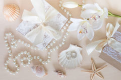 Present, beads, seashells, orchid and rings on wooden background Royalty Free Stock Image