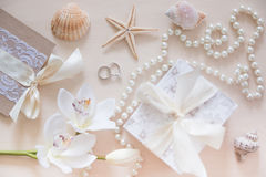 Present, beads, seashells, orchid and rings on wooden background Royalty Free Stock Photos