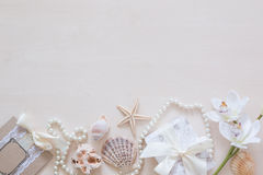 Present, beads, seashells, orchid and space for text on wooden background Royalty Free Stock Photography