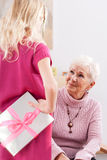 Present for birthday. Young girl giving some present for grandmas birthday Stock Images