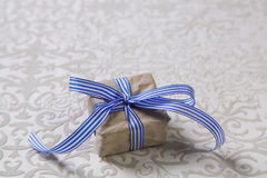Present with blue striped ribbon isolated on grey background. Stock Image
