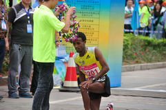 Present a bouquet. Athletes winning the championship is wearing a wreath of congratulations.Half international marathon in fushui county in yunnan province in Royalty Free Stock Images