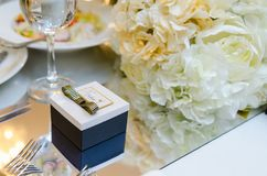 Present box in a bright room. Present box on the table with white flowers in a bright room Stock Photography
