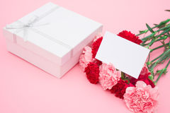 Present box and carnations with a blank card Royalty Free Stock Photography