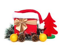 Present box with christmas decoration and santa claus hat on white background Royalty Free Stock Photography