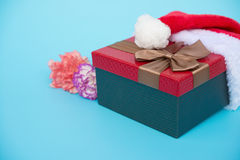 Present box covered by santa claus hat with carnation Stock Image
