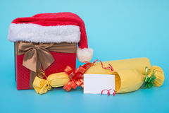 Present box covered by santa claus hat and wrapped wine with blank card for text on blue Stock Photography