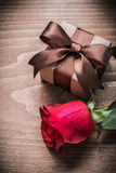 Present box expanded red rose on wooden board holiday concept Royalty Free Stock Photo