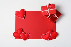 Present box with felt love hearts and greeting card on white wooden background. Valentine`s day celebration concept. Top view. Flat lay royalty free stock photo