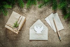 Present box fir tree branch angel paper envelope pencil on sacki Stock Image
