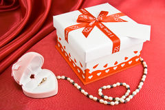 Present box and jewelry. Present on the red background Royalty Free Stock Photos