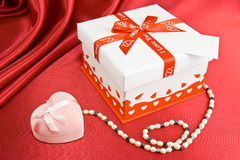 Present box and jewelry. Presents on the red background Royalty Free Stock Photos