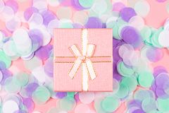 Present box on pink background with multicolored confetti royalty free stock photo