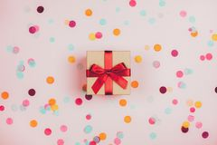 Present box with red bow. On pastel pink background with multicolored confetti. Flat lay style stock image