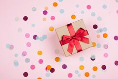 Present box with red bow. On pastel pink background with multicolored confetti. Flat lay style royalty free stock photos