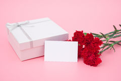 Present box and red carnations with a blank card Royalty Free Stock Photos