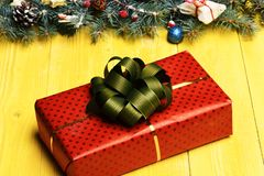 Present box in red color with green bow. Near decorated fir tree branches. Christmas decorations on yellow wooden background. Christmas tree decor. Winter time Royalty Free Stock Images