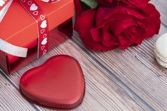 Present box, red rose, and a red heart-shaped metal piece stock photography