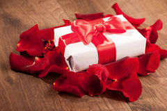 Present box in rose petals on wooden background Stock Photos