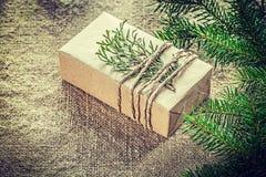Present box thuya pine tree branch on bagging background Stock Photos