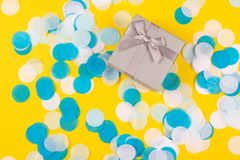 Present box on yellow background with multicolored confetti royalty free stock images