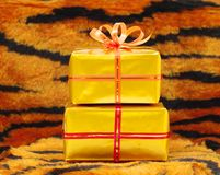 Present boxes. In gold wrap on tiger pattern background Royalty Free Stock Photo