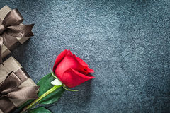 Present boxes with brown ribbon red rose on black background cel Royalty Free Stock Photo