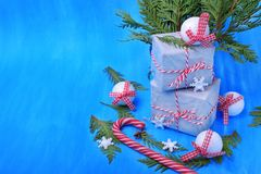 Present boxes, a candy cane, Christmas tree toys and thuja branches against the blue background. Christmas composition royalty free stock images