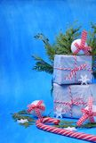 Present boxes, a candy cane, Christmas tree toys and thuja branches against the blue background. Christmas composition royalty free stock image