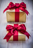 Present boxes in golden paper with red ribbons on wooden board h Royalty Free Stock Images