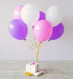 Present boxes and multicolored balloons Stock Photography