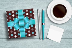 Present with coffee, note, and stationery on desk Royalty Free Stock Images
