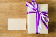 Present with Empty Tag on Wooden Background. Stock Photos
