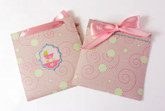 Present envelopes for baby girl. Pink present envelopes for baby girl with pink tape on the white background Royalty Free Stock Photo
